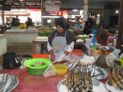 A lady prepares fish