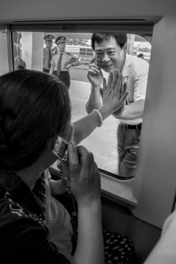 In this 2007 shot, family members say goodbye over the phone as they wave through the window because windows were sealed on the new generation of trains.