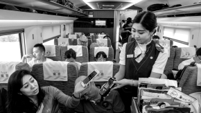 In a 2017 photo, a passenger on a high-speed train pays with her phone.